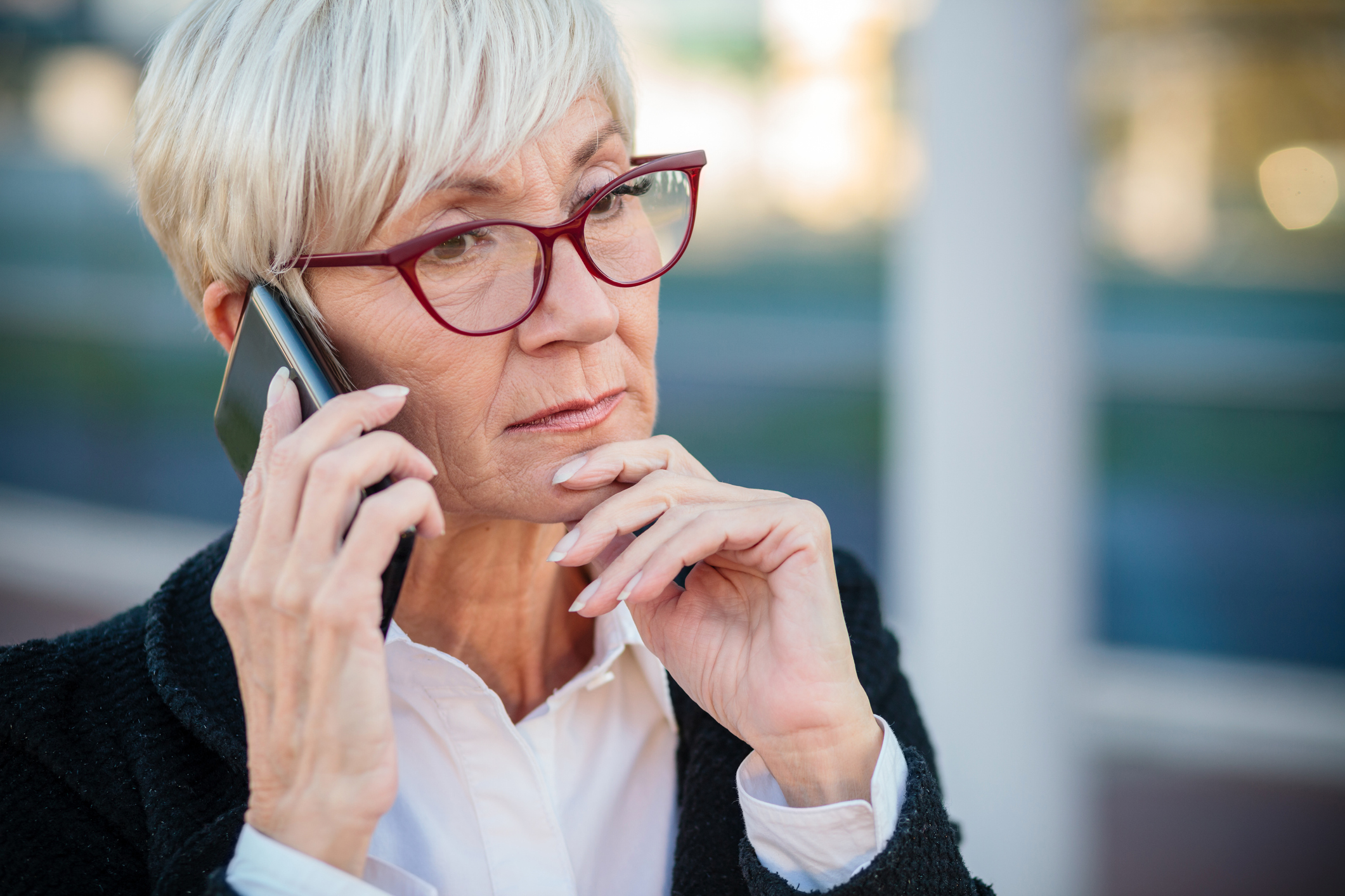 Worried mature businesswoman talking on the mobile phone, resting her arm on chin. Work anywhere concept.